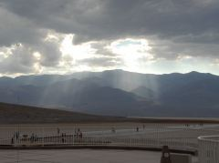 Sonnenlicht bricht durch Gewitterwolken in Badwater, Death Valley